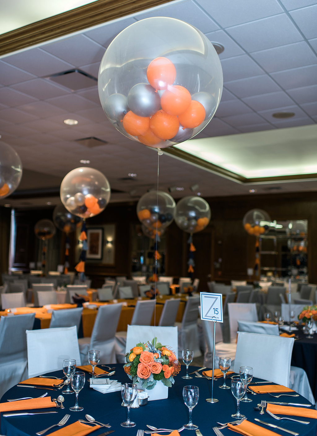Bar Mitzvah Party with Navy tablecloths, navy and orange balloons and orange flowers